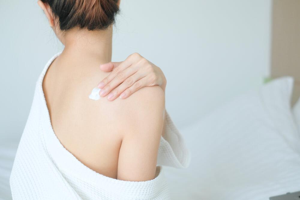 Woman applying cream to back