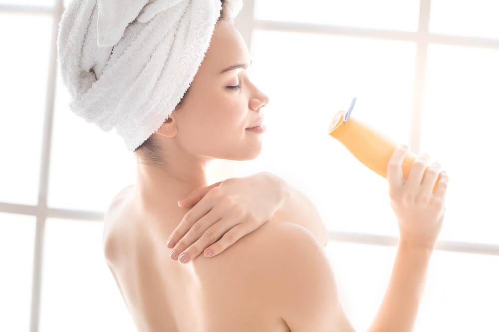 Woman applying body lotion