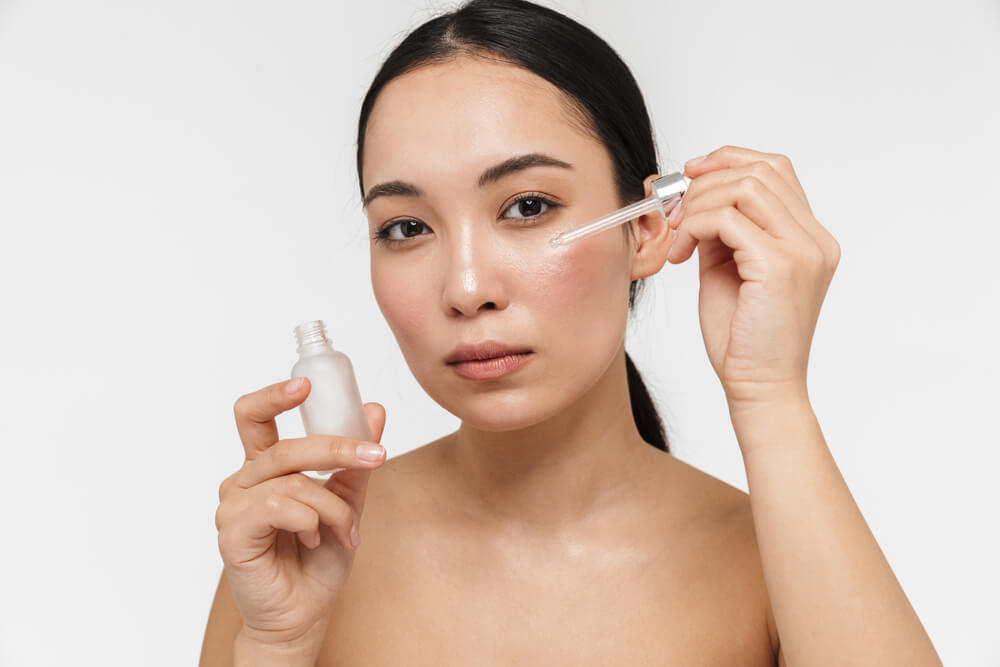 Woman applying face serum